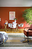 View from living room to dining table against rust-red wall