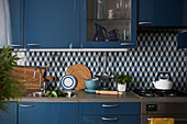 Fitted kitchen with blue fronts and tiled splashback with graphic pattern