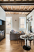 Sofa, round dining table and hideaway kitchen in small interior