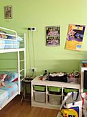 Etagenbett und Aufbewahrungsmöbel mit herausziehbaren Boxen in grünem Kinderzimmer