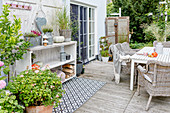 Garden furniture, outdoor rug and wooden shelves on terrace in autumn