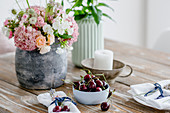 Vase of summer flowers, small bowl of cherries and candle on wooden table
