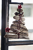 Christmas tree made from pieces of weathered wood tied with red yarn