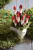 Small Father Christmas figures made from painted branches in container surrounded by moss