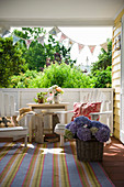 Table, wooden chairs and bunting in seating area on roofed terrace
