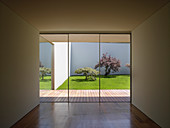 View from cubist, minimalist interior through glass wall onto wooden terrace and courtyard garden