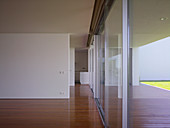 Consecutive doorways between partition walls and glass walls in minimalist house