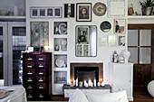 Kaminwand in Weiß mit Nischen und reich dekoriert mit Wandbildern und Dekoobjekten