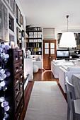 Wohnzimmer in Weiß mit Kommode, Dielenboden und Holztüren als braune Akzente