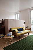 Yellow retro sofa, side table and green rug in front of half-height wooden partition