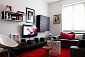 Black furniture and red accents provided by rug and cushions in living room