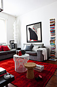 Grey couch, tower bookcase and red accent provided by rug in living room