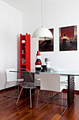 Narrow set of red shelves in corner and glass dining table