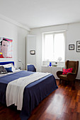 Bedroom with white walls, Pop-art picture on wall and blue bed