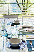 Place settings on glass dining table in front of glass window with garden view