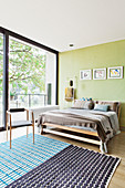 Light-flooded bedroom with glass wall and wooden bed against pastel green wall