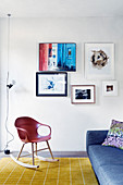 Designer rocking chair and couch next to small gallery of pictures in seating area