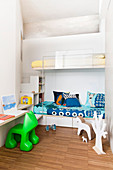 Bunk beds in alcove and shelves used as steps in children's bedroom