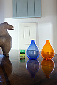 Slow design: terracotta horse and bubble vases on table with abstract artworks on wall in background