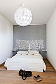White bed and tree of life motif on grey wall in minimalist bedroom