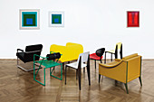Various designer chairs in front of abstract artworks on wall