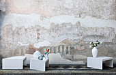 Vases and hand-painted china bird on small, white, designer tables in front of artistically distressed wall