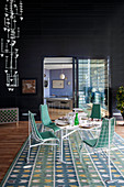 Interior of penthouse apartment with black walls, white metal furniture in dining area and blue and green rug