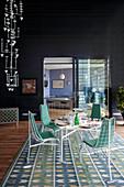 Wohnraum in Penthouse mit schwarzen Wänden und Essbereich mit weißen Metallmöbeln auf blau-grünem Vintage-Teppich