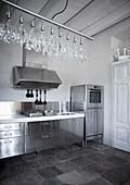 Edelstahlküche in Landhaus mit Fliesenboden und modernem Kronleuchter