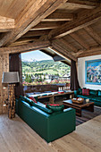 Green leather sofas in living room of rustic wooden house