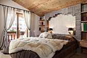 Fur blanket on bed in rustic bedroom with log-cabin charm