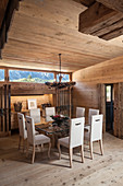 Chairs with white upholstery around glass dining table in rustic wooden house