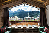 View of mountain village through panoramic window of chalet