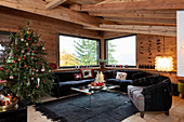 Decorated Christmas tree and black sofa set in living room of chalet