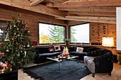 Geschmückter Weihnachtsbaum und schwarze Polstermöbel im Wohnzimmer eines Chalets