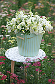 A white bouquet of dahlias, snapdragons, and bergamot in a tin bucket