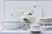 Vase of white carnations and hydrangeas and china crockery on dresser