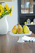 Pear on cake stand on dining table