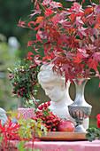 Herbstliches Stillleben mit Zierahorn, Hagebutten und Mädchenbüste im Garten