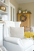 White armchair in living room with autumnal decorations