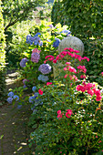 Bed with roses and hydrangeas along the way, granite column with ball