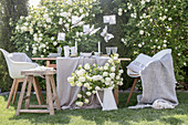 Table set in white and beige in garden in front of viburnum bush