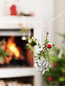 Weihnachtsdekoration aufgehängt an Schnur vorm Kamin