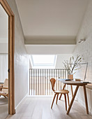 Desk and chair against whitewashed brick wall