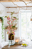 Autumn arrangement of spindle seed pods and fennel flowers on dining table