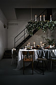 Festively decorated, candlelit dining table in loft interior