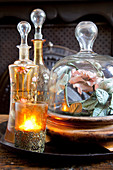 Tealight holder, antique carafes and rose under glass cover on tray