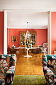 Eclectic furnishings in classic dining room with coral-red walls