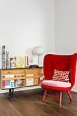 Red armchair providing a splash of colour and retro sideboard in reading area