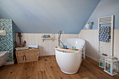 Free-standing bathtub in maritime bathroom with white wainscoting